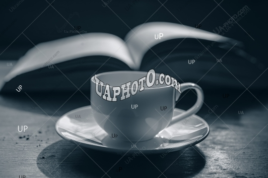 cup of coffee on the background of an open book.