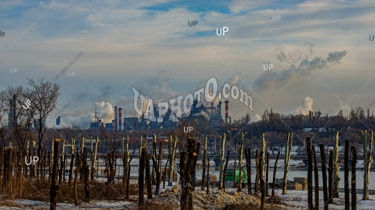 Destroyed park area against the background of a metallurgical pl