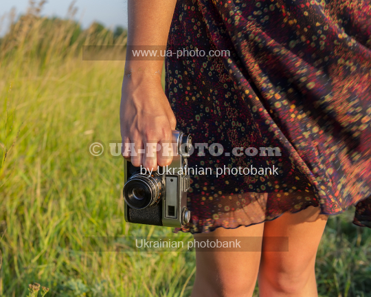 Girls legs and hand with  camera. Travel with a camera.