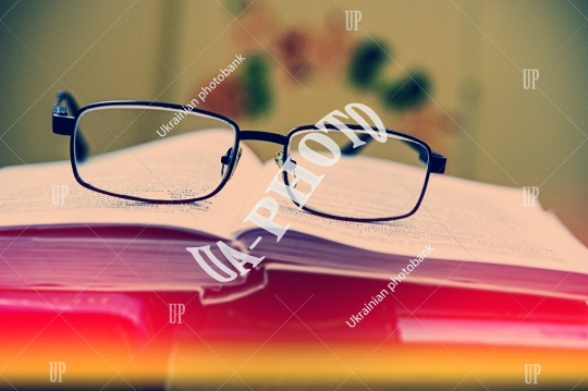 Glasses lie on the pages of an old open book