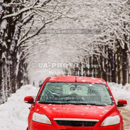 red car stands on a snowy street